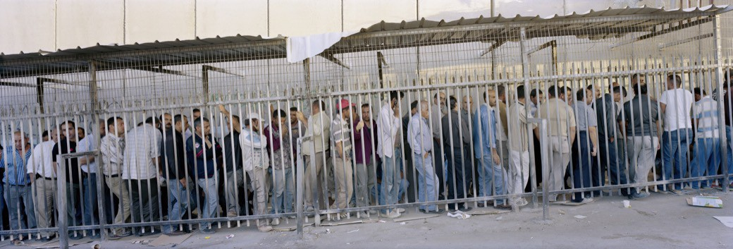 59_1422IL_Palestinians_cueing_fence_wall